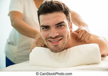 Happy Latin man getting a massage