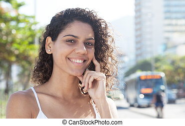 Happy latin woman outside in the city looking at camera