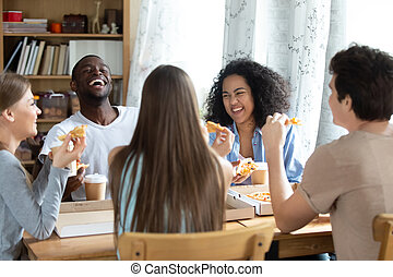 Happy laughing African American man, enjoying pizza with friends