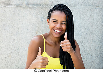 Happy laughing african american woman with dreadlocks showing thumbs