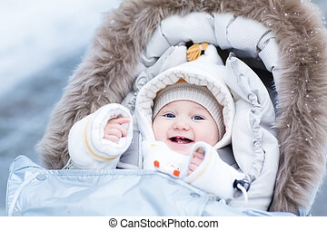 Happy laughing baby girl enjoying a walk in a snowy winter...