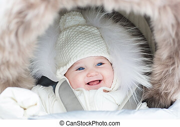 Happy laughing baby girl in a warm stroller wearing a winter jac