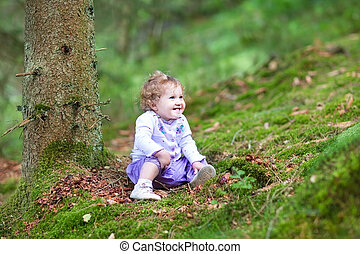 Happy laughing baby girl playing in a beautiful pine wood forest