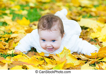 Happy laughing baby girl playing in an autumn park on yellow lea