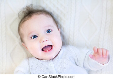 Happy laughing baby girl relaxing on a warm knitted blanket