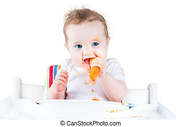 Happy laughing baby girl trying her first solid food, a carrot,