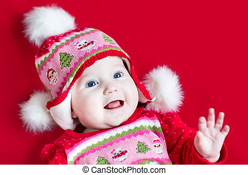 Happy laughing baby girl with beautiful blue eyes wearing a Chri
