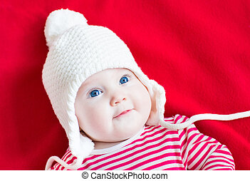 Happy laughing baby girl with beautiful blue eyes wearing a whit