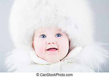 Happy laughing baby in a big fur hat and white snow jacket