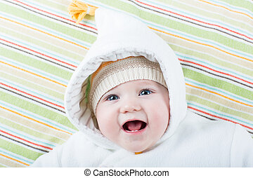 Happy laughing baby in a warm jacket with a funny hat