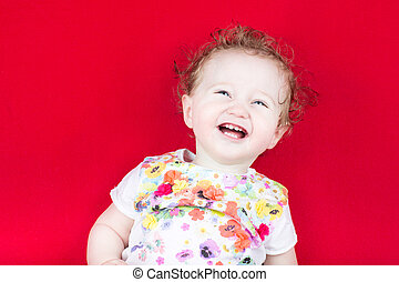 Happy laughing baby on a red blanket