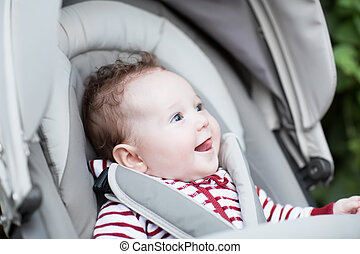 Happy laughing baby sitting in a stroller