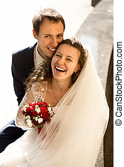 happy laughing bride and groom on street at sunny day