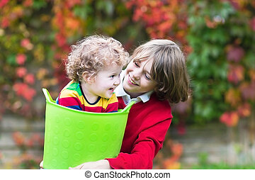 Happy laughing brother and baby sister playing together in the g