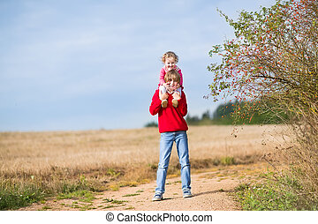 Happy laughing brother and his baby sister playing together in a
