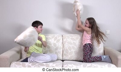 Happy laughing brother and sister having a pillow fight