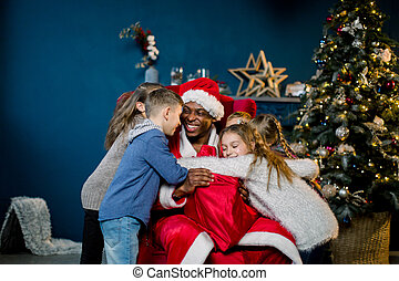 Happy laughing children hugging African Santa Claus sitting on a red chair on the background of a Christmas tree and decorations.