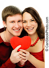 happy laughing couple with a heart-shaped pillow in their hands