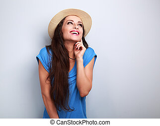 Happy laughing excited woman in hat looking up on blue background
