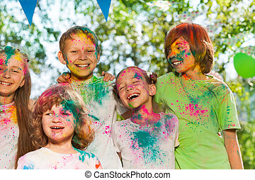 Happy laughing kids smeared with colored powder