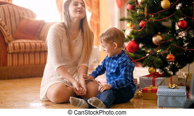 Happy laughing little boy throwing colorful confetti with mother on Christmas morning at living room