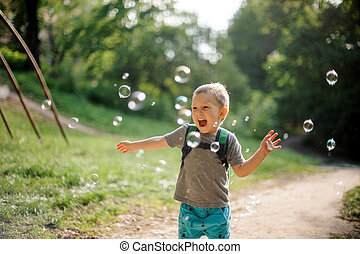 Happy laughing little boy with soap bubbles in summer park on sunny day