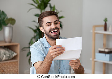 Happy laughing man holding paper notification, letter with good news