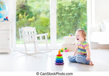 Happy laughing toddler girl playing in a white room with a big w