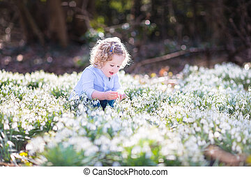 Happy laughing toddler girl playing with first spring flowers