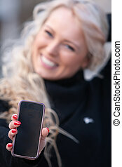 Happy laughing woman holding out her mobile