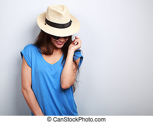 Happy laughing woman in glasses and fashion hat looking down on blue background
