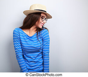 Happy laughing woman in glasses and straw hat looking down on blue background