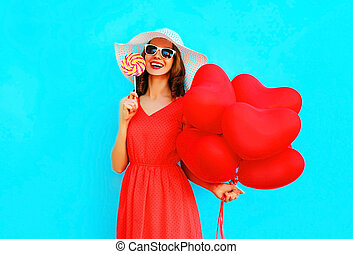 Happy laughing woman in hat with a lollipop candy, air balloons on blue background