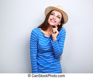 Happy laughing woman in straw hat thinking and looking up on blue background with empty copy space