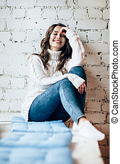 Happy laughing woman relaxing on window sill