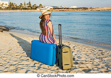 Happy laughing woman tourist sitting in front of the sea on blue suitcase. Travel and summer vacation concepts.