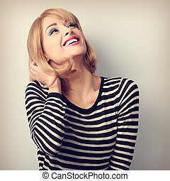 Happy laughing young blond woman looking up
