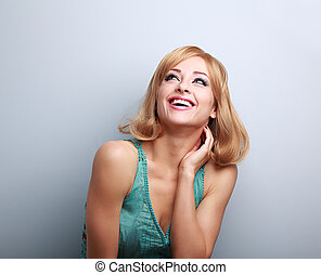 Happy laughing young blond woman with short hair looking up