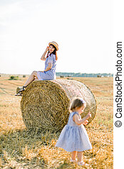 Happy laughing young mother in straw hat and striped dress sitting on hay stack and looking at her cute little daughter playing with wheat spikelets in beautiful summer harvested field
