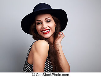 Happy laughing young woman in black hat looking on blue background