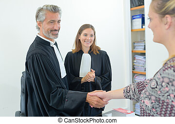 happy lawyers shaking hands with client