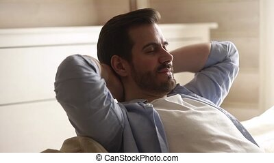 Happy lazy young man relax daydream meditate sit on sofa -...