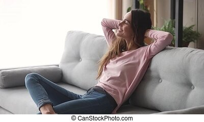 Happy lazy young woman relaxing sitting on couch at home -...