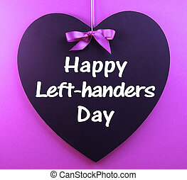 Happy Left-handers Day message sign text written on heart shape blackboard hanging against a purple background for International Left-handers Day celebrated on August 13.