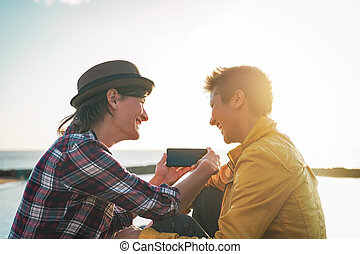 Happy lesbian couple watching on mobile phone next the beach at sunset - Young homosexual women having fun with new trends technology - Lgbt, homosexuality, tech and relationship concept