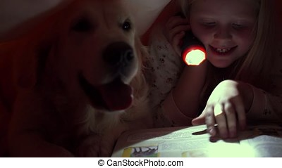 happy life with pets - little children at night reading a book under the covers with their big dog