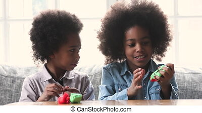 Happy little african american children playing with colorful plasticine.
