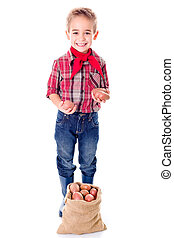 Happy little agriculturist boy showing potato harvest