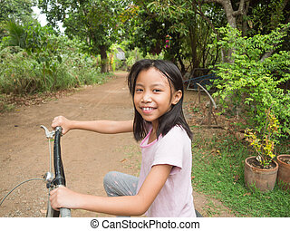Happy little asian kid riding bicycle in the park