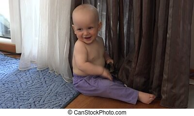 Happy little baby boy in pants play near curtain. Smiling boy looking at camera